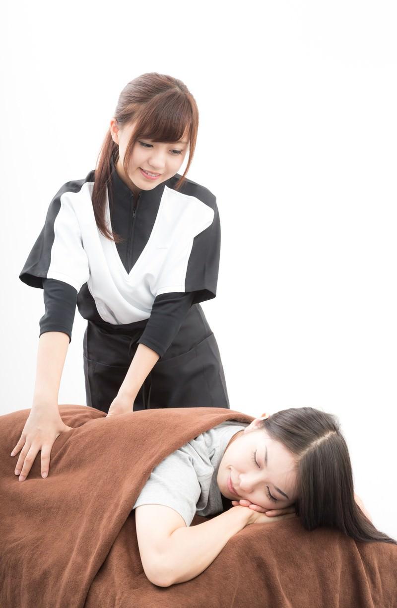 「背中を施術する女性スタッフ」の写真[モデル:河村友歌]