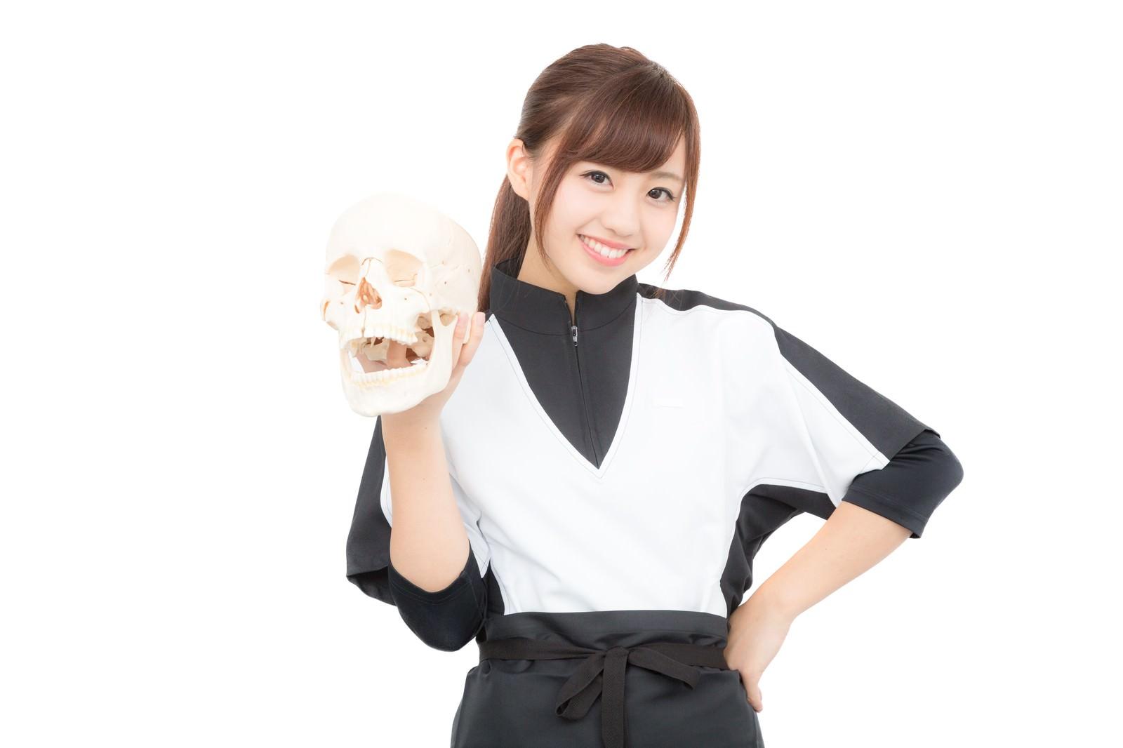 「ドクロを持った笑顔の女性スタッフドクロを持った笑顔の女性スタッフ」[モデル:河村友歌]のフリー写真素材を拡大