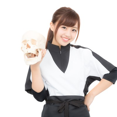 ドクロを持った笑顔の女性スタッフの写真