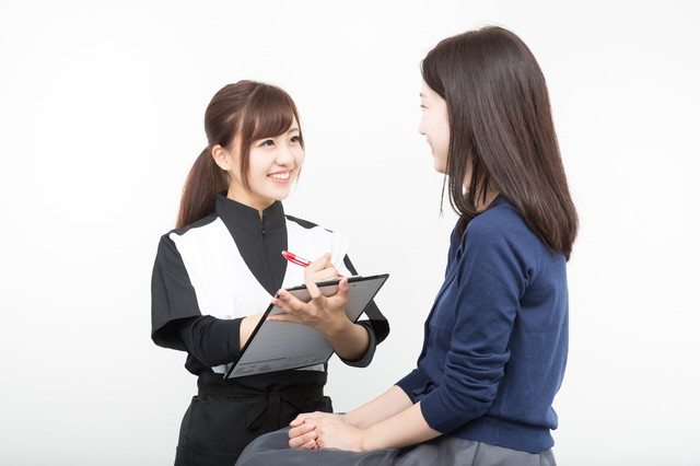 患者の体調を問診する女性スタッフの写真