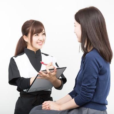 「患者の体調を問診する女性スタッフ」の写真素材