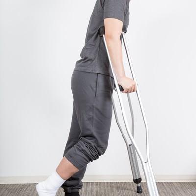 「右足を捻挫して松葉杖の男性」の写真素材