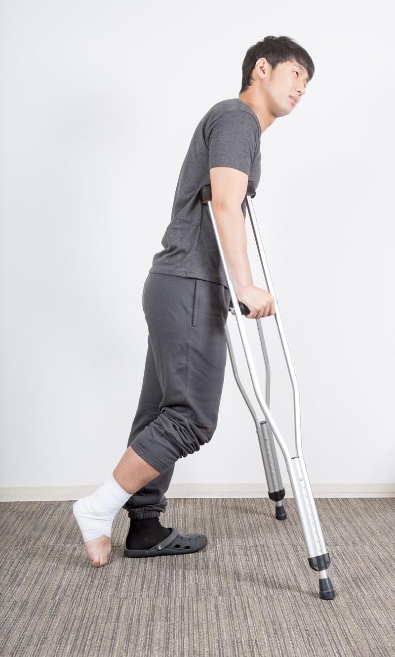「右足を捻挫して松葉杖の男性」の写真[モデル:大川竜弥]