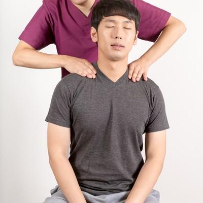 「肩こりで来院した男性と施術する柔道整復師」の写真素材