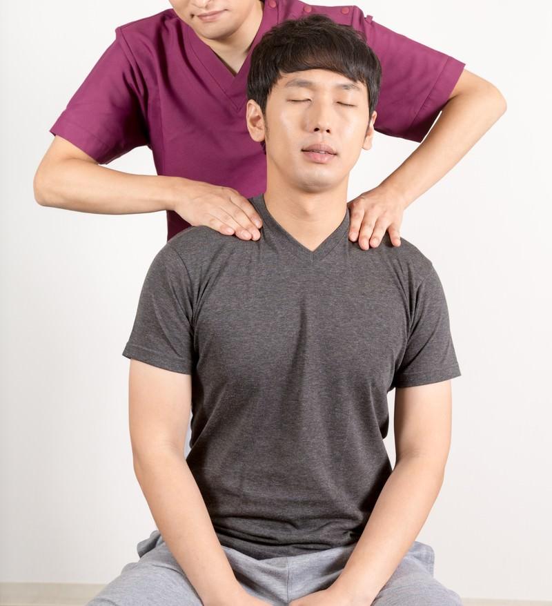 「肩こりで来院した男性と施術する柔道整復師」の写真[モデル:大川竜弥]
