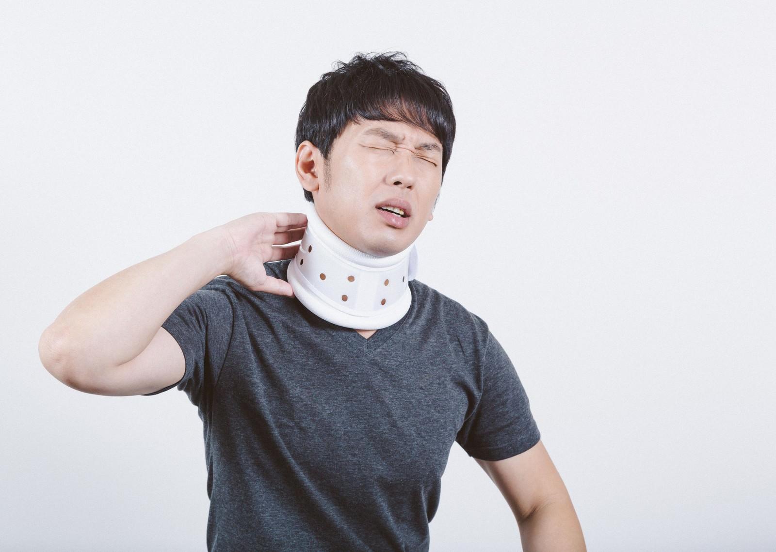 「交通事故のむち打ちで首にコルセットを巻く男性」の写真[モデル:大川竜弥]