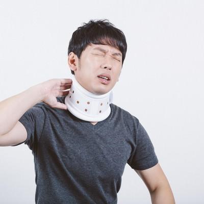 「交通事故のむち打ちで首にコルセットを巻く男性」の写真素材