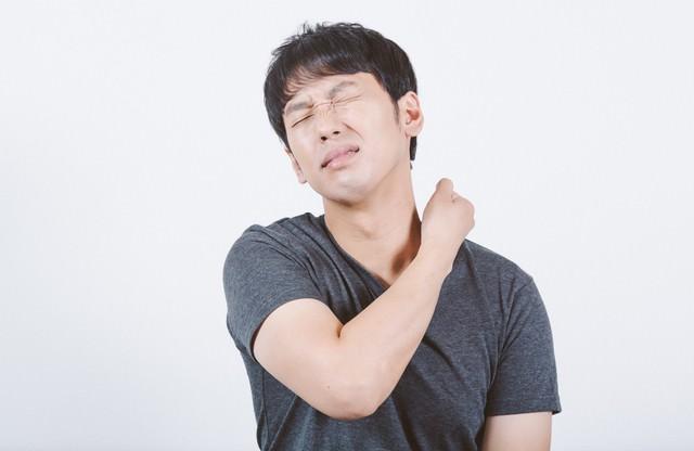 首の痛みや違和感を感じる男性の写真