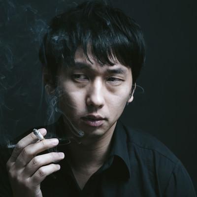 暗い喫煙室で煙草を吸う男性の写真