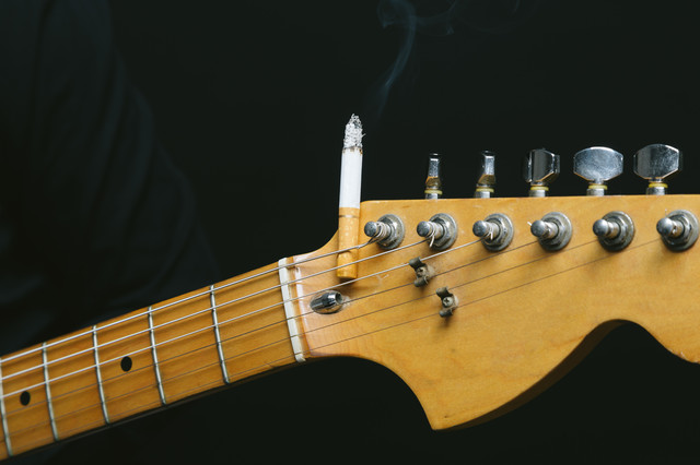 ギターのヘッドにタバコを挟む(焦げあと注意)の写真