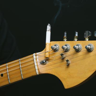 「ギターのヘッドにタバコを挟む(焦げあと注意)」の写真素材