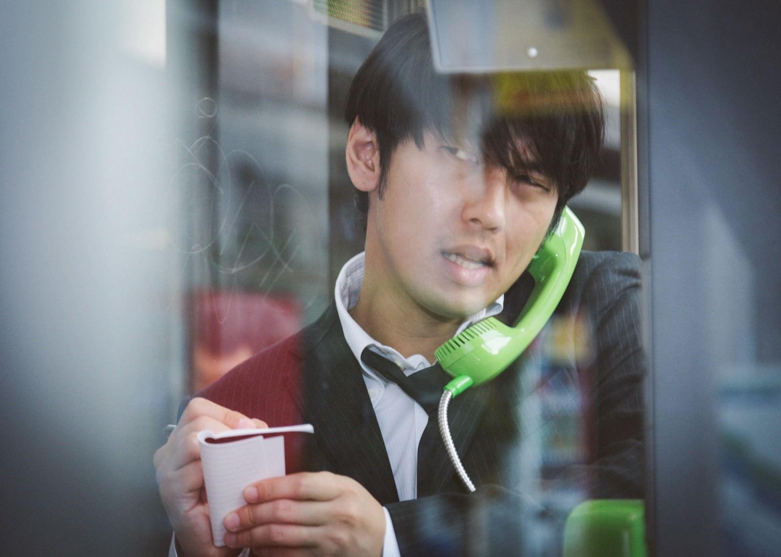 「電話ボックスのピンクチラシが気になるブン屋」の写真[モデル:大川竜弥]