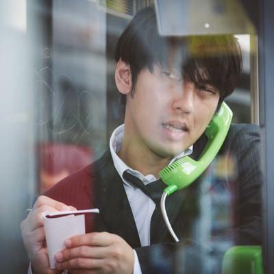 「電話ボックスのピンクチラシが気になるブン屋」の写真素材