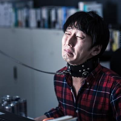 首輪を繋がれ泣きながら残業する若きエンジニアの写真