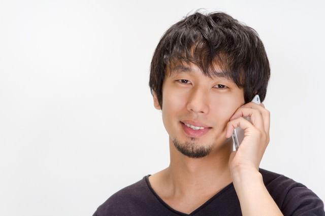 「今何やってるの?」と電話をかける男性の写真
