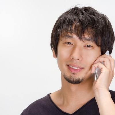 「「今何やってるの?」と電話をかける男性」の写真素材