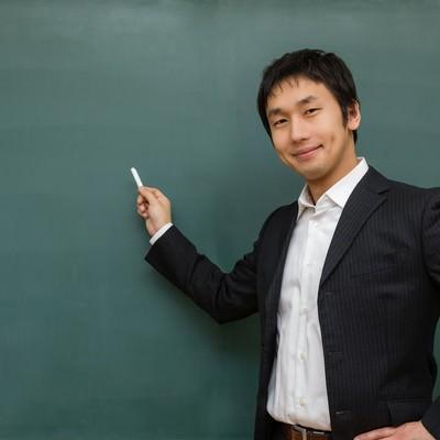 「ニコニコしながら授業をする先生」の写真素材