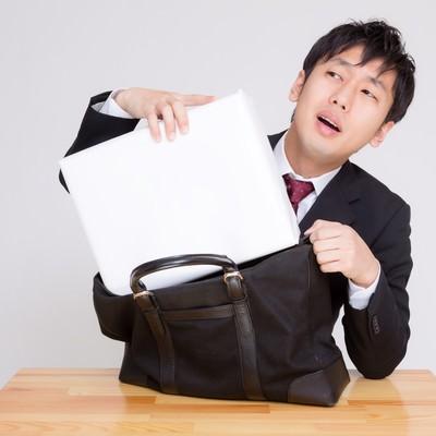 「札束に見立てた箱がかばんに入らない男性」の写真素材