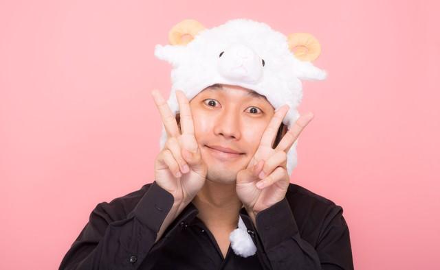 新年を喜ぶ羊の帽子をかぶった男性の写真