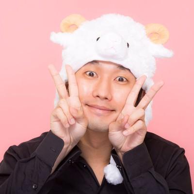 「新年を喜ぶ羊の帽子をかぶった男性」の写真素材