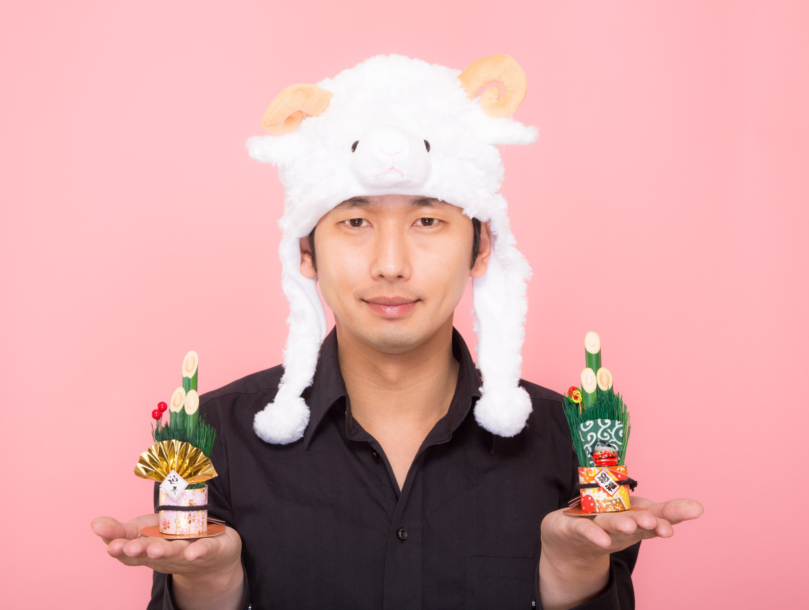 「新年!門松を両手に持った羊帽をかぶった男性」の写真[モデル:大川竜弥]