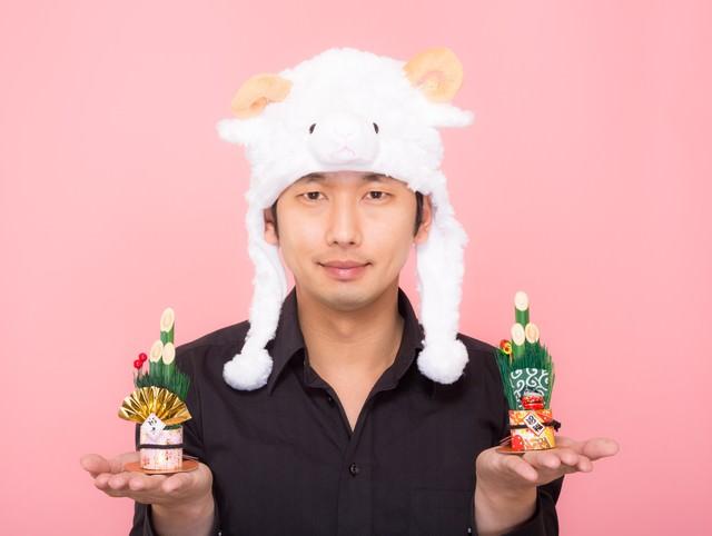 新年!門松を両手に持った羊帽をかぶった男性の写真