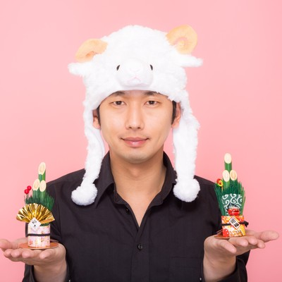 「新年!門松を両手に持った羊帽をかぶった男性」の写真素材