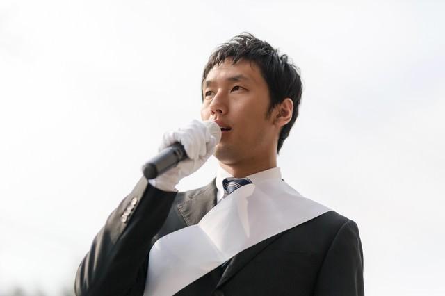 街宣車の上から演説する立候補者の写真