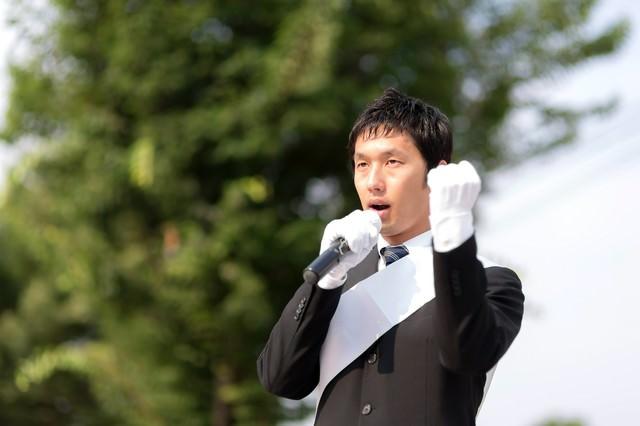 拳を握り、憲法改正を訴える立候補者の写真