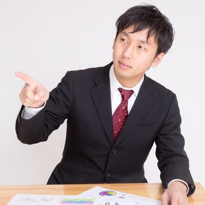 「資料を見て問題点を指摘する男性」の写真素材
