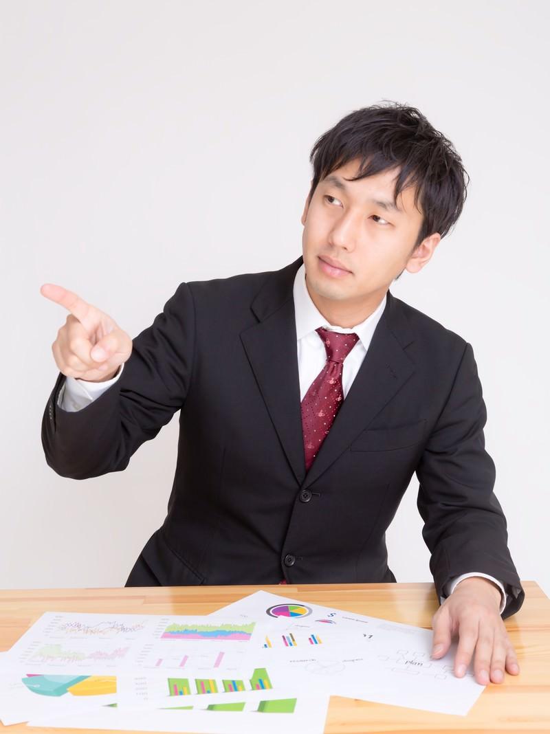 「資料を見て問題点を指摘する男性」の写真[モデル:大川竜弥]