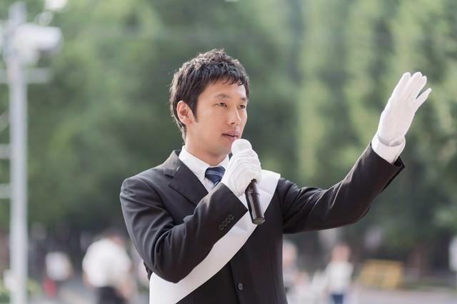 タスキをかけて街頭演説をする男性の写真