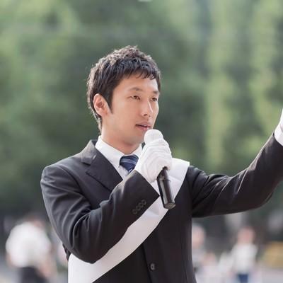 「タスキをかけて街頭演説をする男性」の写真素材