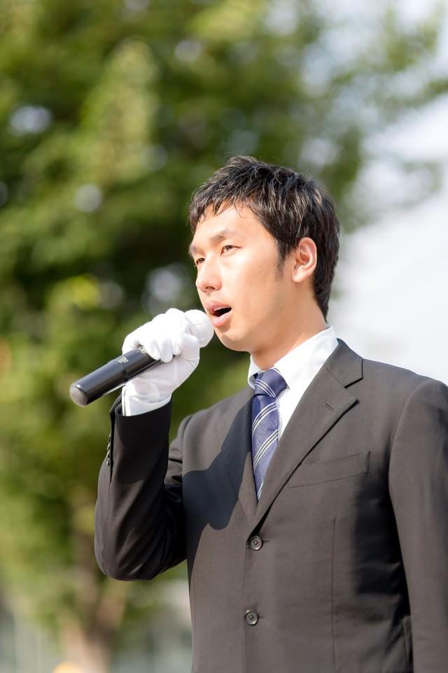 街灯演説するマイクを持った若い立候補者の写真