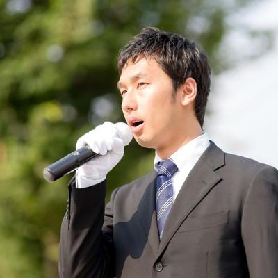 「街灯演説するマイクを持った若い立候補者」の写真素材