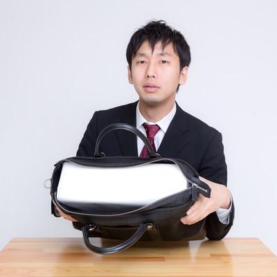 札束に見立てた白い箱がかばんに入ったと説明するビジネスマンの写真
