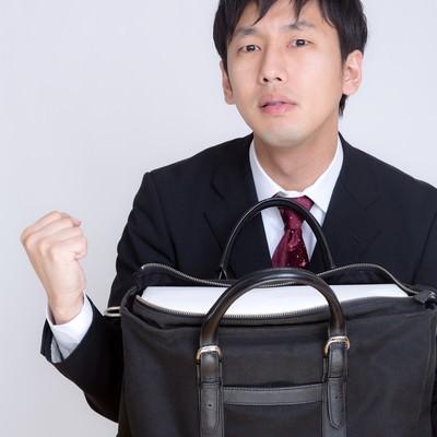 「かばんに白い箱が入ってガッツポーズを決めるビジネスマン」の写真素材