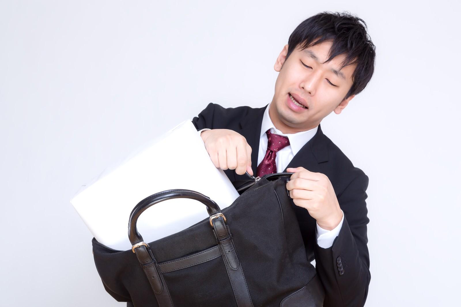 「縦なら入るとファスナーを閉めようとするビジネスマン」の写真[モデル:大川竜弥]