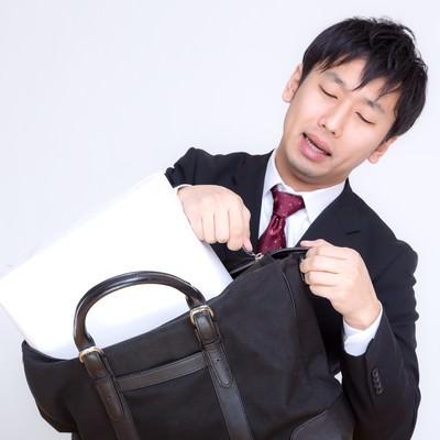 「縦なら入るとファスナーを閉めようとするビジネスマン」の写真素材