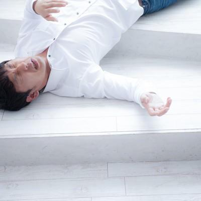 「熱中症で倒れ込み苦しむ男性」の写真素材