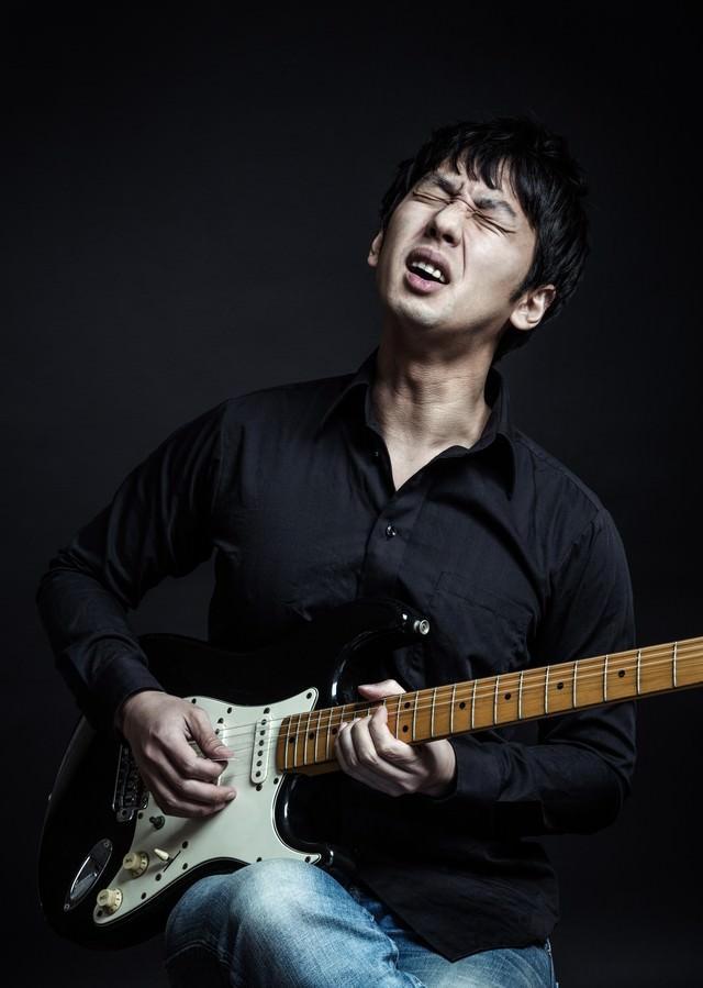 顔でチョーキングするブルースギタリストの写真