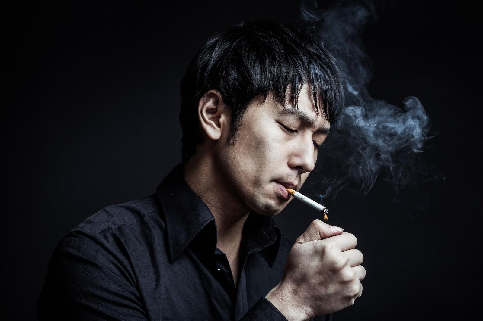 「指先でタバコに火をつける新進気鋭のマジシャン」の写真[モデル:大川竜弥]