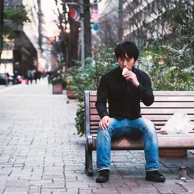 「鳩にパンをあげる心優しい青年」の写真素材
