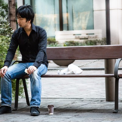 「ベンチでぼっち飯をする映画俳優」の写真素材