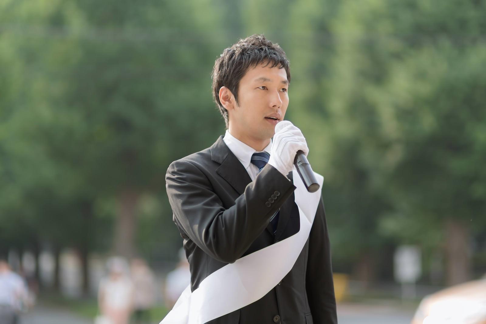 「マイクでスピーチする政治家」の写真[モデル:大川竜弥]