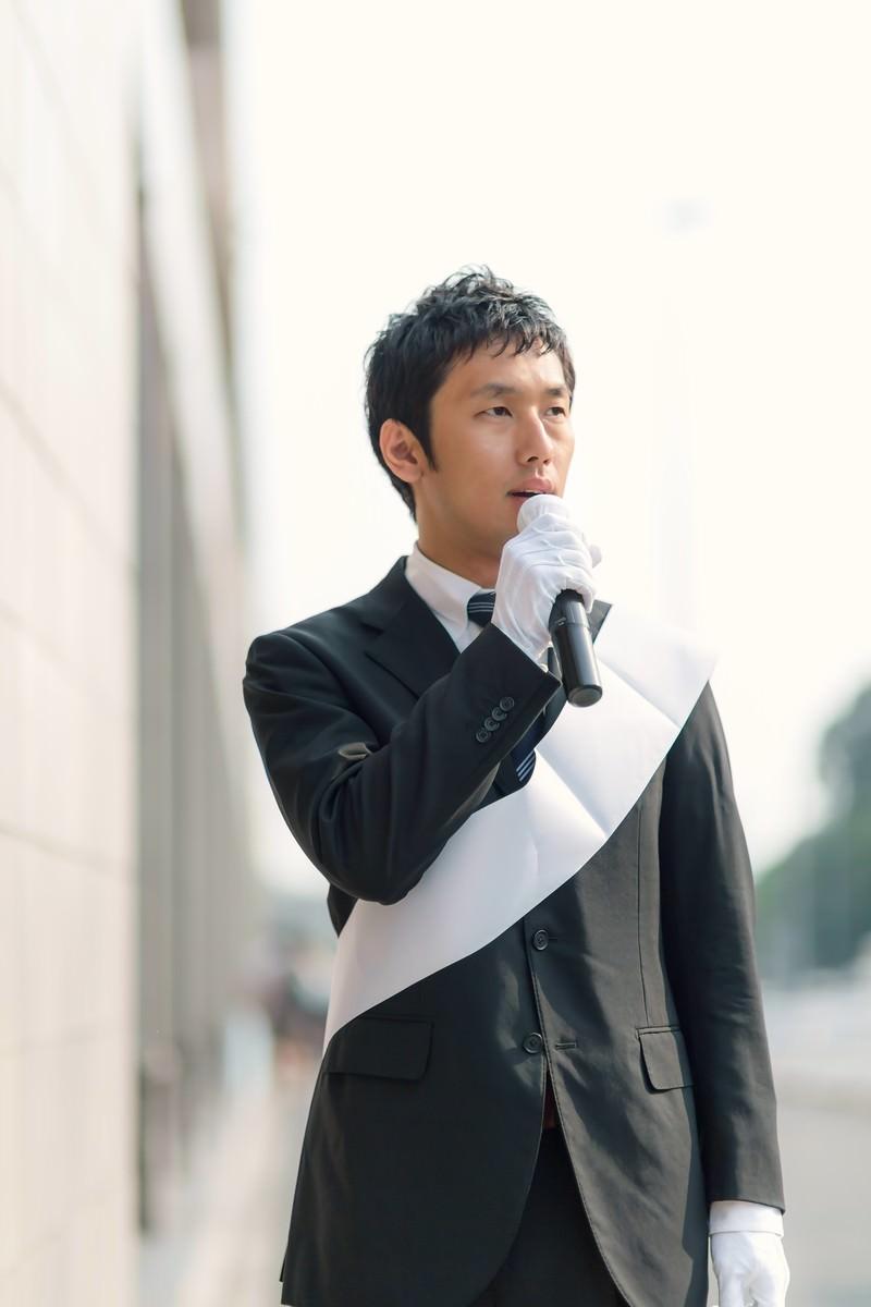 「マイクを握り街頭演説する立候補者」の写真[モデル:大川竜弥]