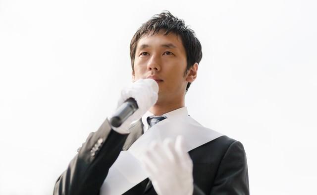 消費税増税と国民の生活について街宣車の上から演説する立候補者の写真