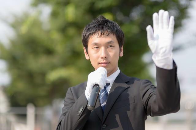 手を振りクリーンなイメージをPRする若い政治家の写真