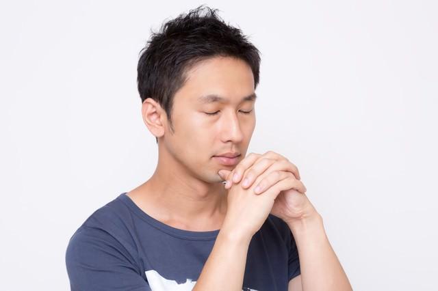 「お願い!」っと手を組んで祈る男性の写真