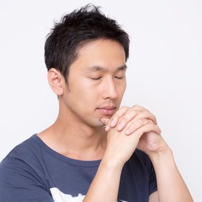 「「お願い!」っと手を組んで祈る男性」の写真素材